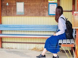 建物の前のベンチに座っている人の写真・画像素材[2232370]