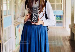 鏡の前に立つ人がカメラに向かってポーズをとるの写真・画像素材[2232372]