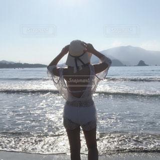 水域の近くの浜辺に立つ女性の写真・画像素材[2353915]
