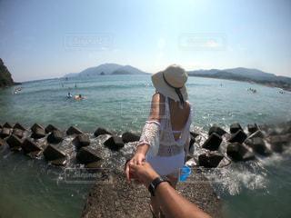 水の体の隣に立っている女性の写真・画像素材[2372650]