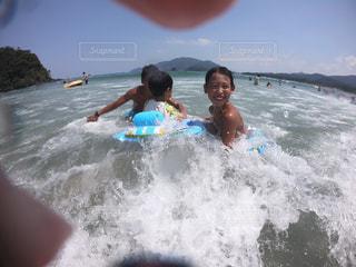 水の中のサーフボードに波に乗っている若い女の子の写真・画像素材[2372654]