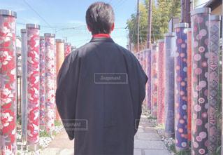 赤いジャケットを着た男がカメラを見ているの写真・画像素材[2392884]