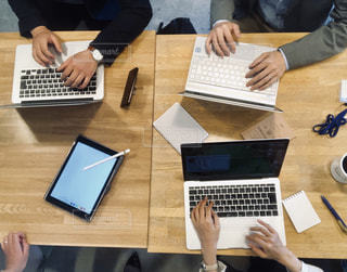 ラップトップコンピュータを使ってテーブルに座っている人々のグループの写真・画像素材[2443430]