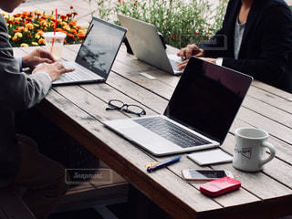 ラップトップを使ってテーブルに座っている人々のグループの写真・画像素材[2443436]