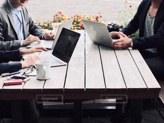 ノートパソコンを持ってテーブルに座っている人々のグループの写真・画像素材[2445062]