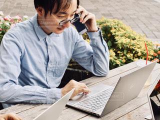 ラップトップコンピュータを使ってテーブルに座っている人の写真・画像素材[2447279]