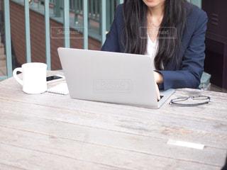 ノートパソコンの前のテーブルに座っている人の写真・画像素材[2447280]