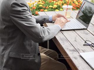 ノートパソコンを使ってテーブルに座っている男の写真・画像素材[2447281]
