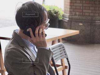 携帯電話で話している椅子に座っている人の写真・画像素材[2447289]