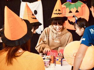 誕生日の帽子をかぶったテーブルに座っている人々のグループの写真・画像素材[2509192]