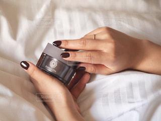 電話を使ってベッドに横たわっている人の写真・画像素材[2920645]