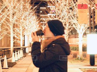 男性,1人,飲み物,風景,冬,夜,夜景,コーヒー,屋外,大阪,帽子,光,イルミネーション,横顔,人,カップ,寒い,歩道,地面,明るい,コーヒーカップ,グランフロント,飲む