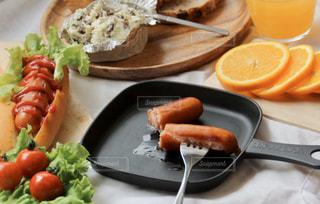 食べ物の皿をテーブルの上に置くの写真・画像素材[3214627]