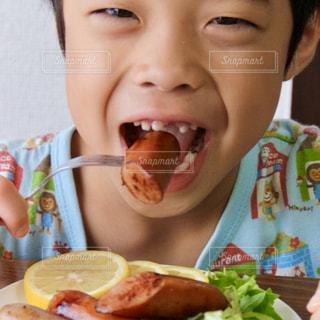 食べ物を食べている小さな男の子の写真・画像素材[3268936]