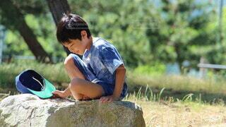 岩の上に座っている少年の写真・画像素材[4636749]
