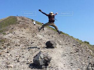 岩が多い丘の上に空気を通って飛んで人の写真・画像素材[1405716]