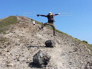 岩が多い丘の上に空気を通って飛んで男の写真・画像素材[1405717]