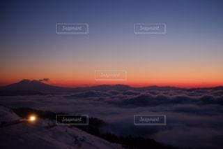 背景にオレンジ色の夕日の写真・画像素材[1410643]