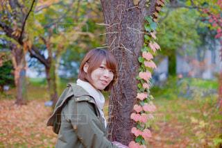 木の隣に立っている女の子の写真・画像素材[1637976]