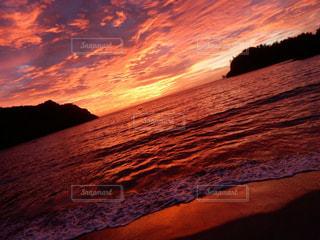 背景の山が付いている水の体に沈む夕日の写真・画像素材[962933]
