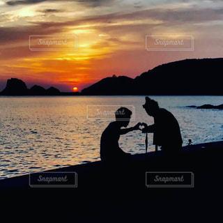 夕日とカップルの写真・画像素材[775136]