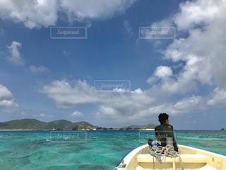水の体の横に立っている人の写真・画像素材[1389023]