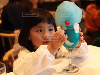 小さな女の子のテーブルに座っての写真・画像素材[894626]