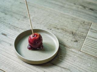 木製のテーブルの上に座っている赤いリンゴの写真・画像素材[2499421]