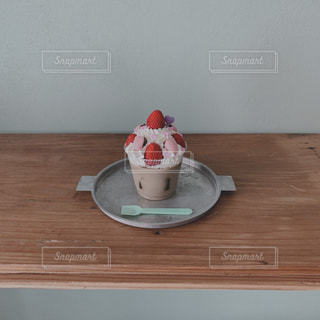 木製のテーブルに苺パフェの写真・画像素材[3304379]