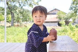 ピクニック用のテーブルに座っている小さな男の子の写真・画像素材[1362707]