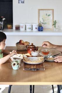 食べ物を持ってテーブルに座っている人の写真・画像素材[3281127]