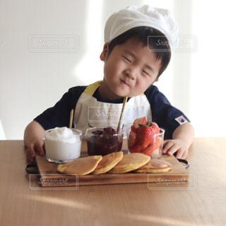 食べ物を食べるテーブルに座っている小さな男の子の写真・画像素材[3281131]