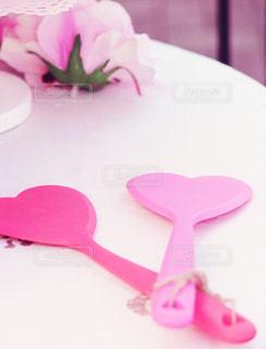 テーブルの上のピンクの花をのせたプレートの写真・画像素材[1117837]