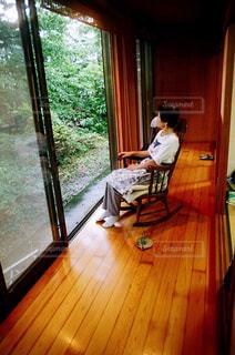 窓の前のテーブルに座っている男の写真・画像素材[743580]