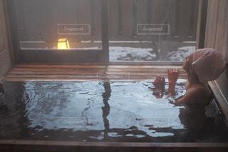 窓の前でベンチに座っている人の写真・画像素材[752820]