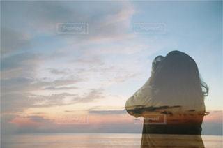 空を見上げると女性の写真・画像素材[956153]