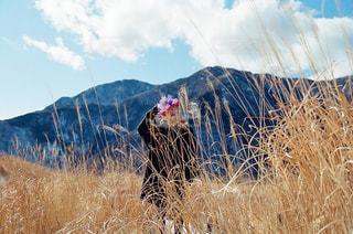 乾いた草のフィールドに立っている人の写真・画像素材[1017742]