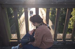 ウィンドウの横にあるベンチに座っている人の写真・画像素材[1017743]