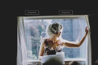 窓の前に座ってる女性。の写真・画像素材[2181498]