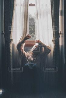 カーテンの前に座っている女性。の写真・画像素材[2181502]