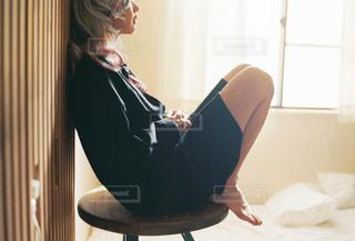 窓の前に座っている女性の写真・画像素材[2860994]