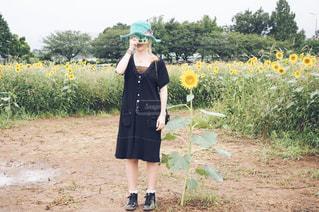 ひまわり畑に立っている女性の写真・画像素材[2860998]