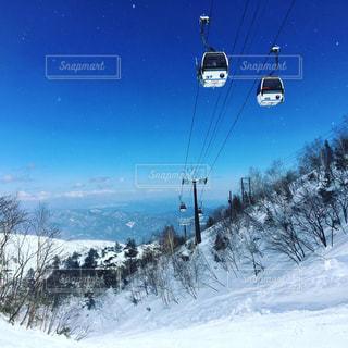 雪の上に空気を通って飛んで男覆われた斜面の写真・画像素材[886478]