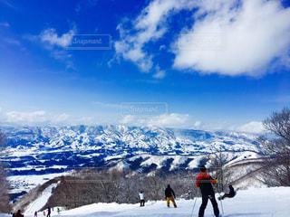 雪に覆われた斜面をスキーに乗っている人のグループ - No.929281