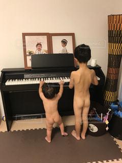 ピアノの前に立っている少年の写真・画像素材[817330]
