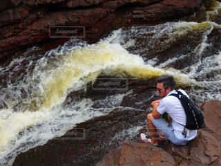 滝の隣に立っている男の写真・画像素材[776664]