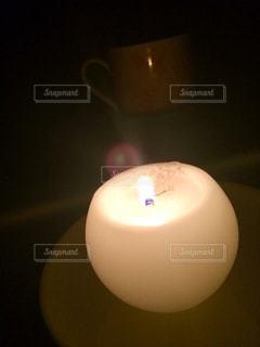 暗い部屋でボールと白いろうそくの写真・画像素材[910855]