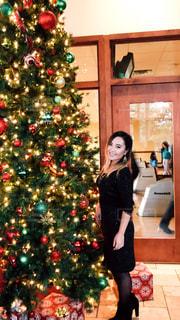 クリスマス ツリーの前に立っている女性 - No.937596