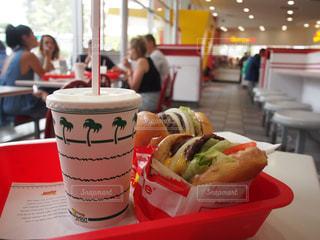 テーブルの上にあるハンバーガーとシェイクのセットの写真・画像素材[803281]