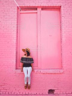 ピンクのドアの前に座っている女性の写真・画像素材[842469]
